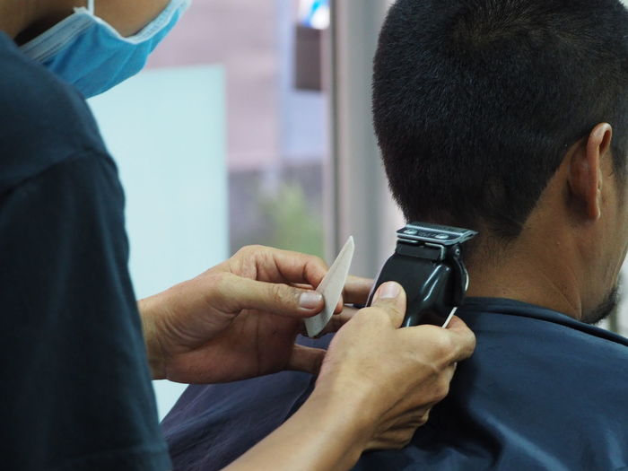 Cropped hands of man cutting customer hair in salon