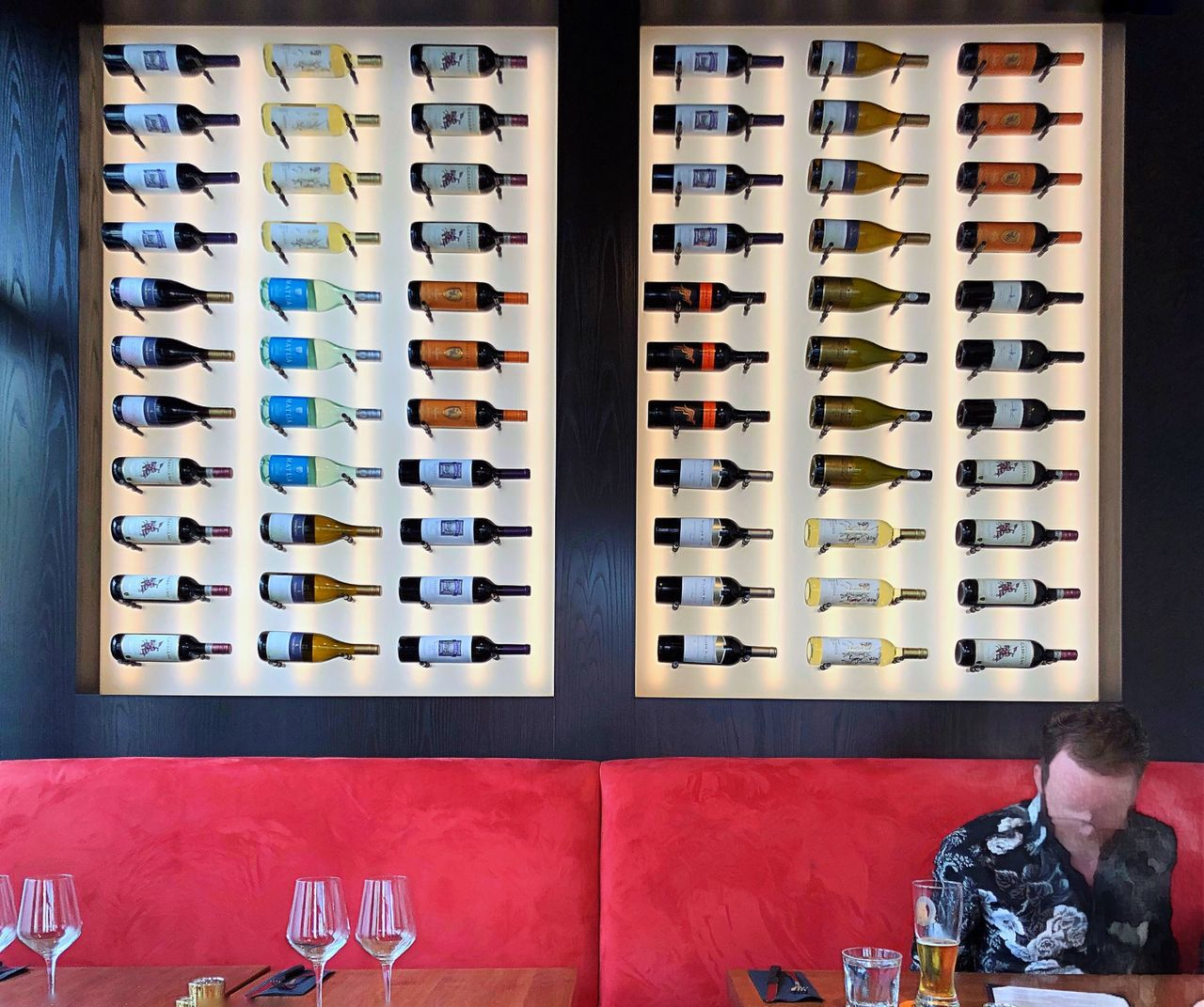 LOW ANGLE VIEW OF WINE BOTTLES ON TABLE AT RESTAURANT