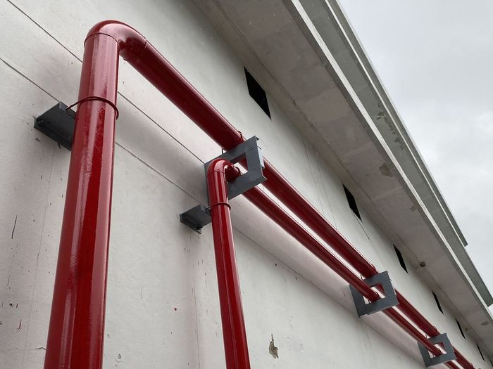 Low angle view of pipes against wall