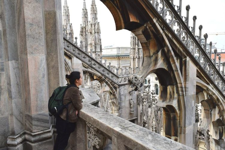 Woman standing by retaining wall at milan cathedral