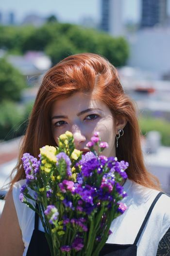 Portrait of young woman with purple flowers against blurred background