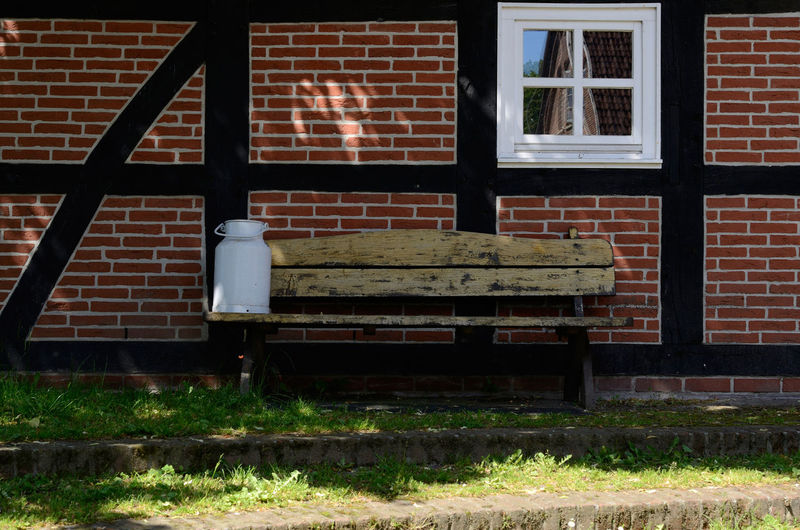 Milk can on an old bench Agriculture Architecture Brick Wall Building Exterior Built Structure Day Farm House Grass Milk Can No People Outdoors Sunset Sunshine Traditional Window