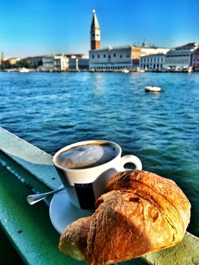 Close-up of breakfast on railing by river in city against clear sky