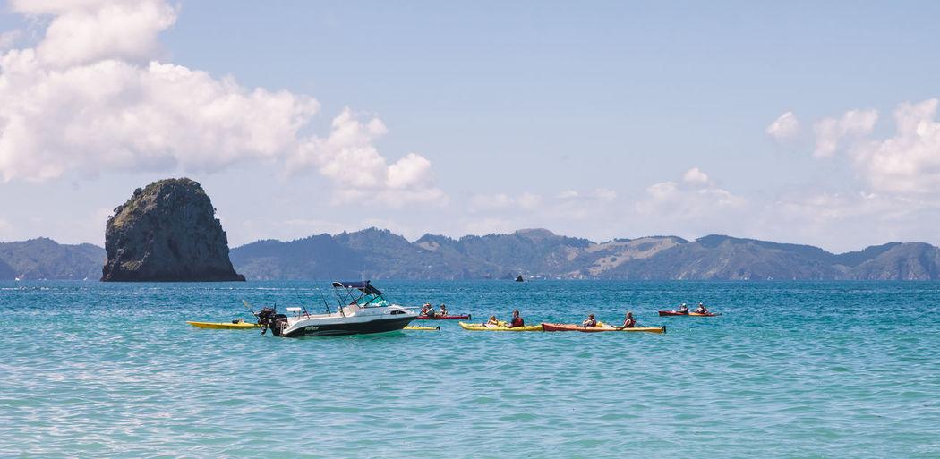 People Kayaking In Sea Against Sky