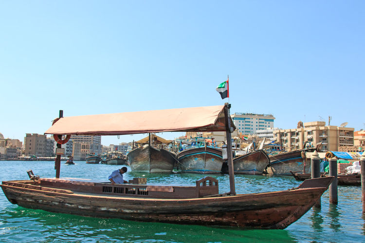 Dubai, UAE - October 08, 2014: People are commuting and using traditional wooden boat at dubai creek of UAE Architecture Blue Boat Building Exterior Built Structure Canal Clear Sky Day Dubai Dubai Creek Emirates Famous Place Flag Old Outdoors Rich Riverbank Sea Tourism Tourists Travel Destinations United Arab Emirates Water Waterfront Wide Shot