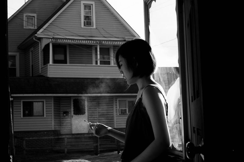 Side View Of Young Woman Smoking While Standing In Balcony