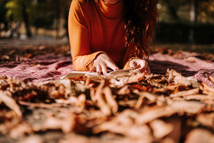 Midsection of woman with autumn leaves on land