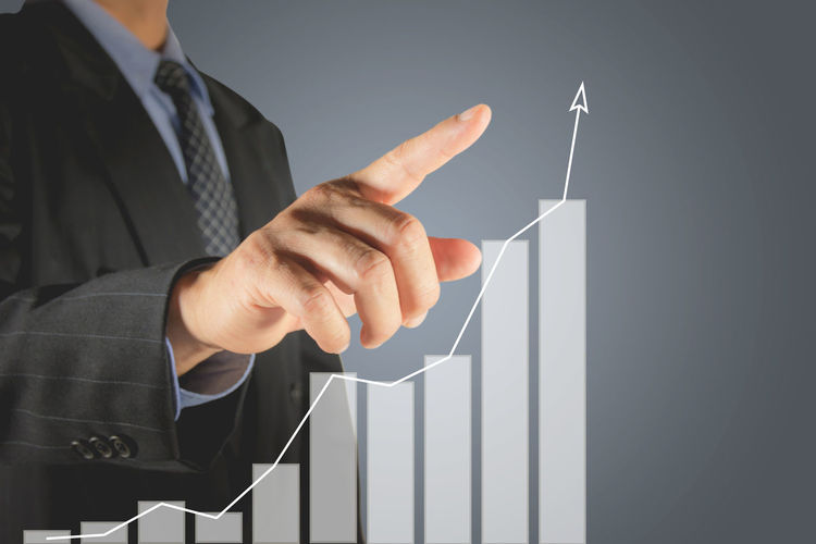 Digital composite image of businessman examining graph against gray background