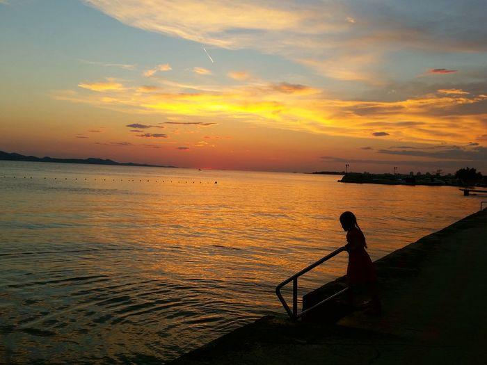 Silhouette girl on pier against sky during sunset