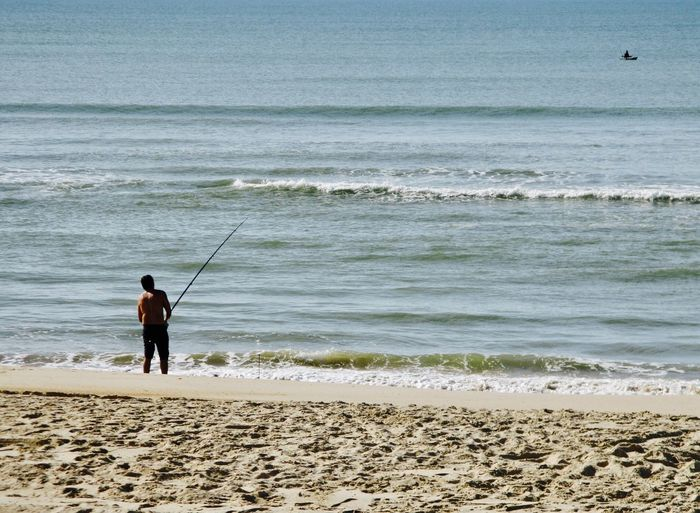 Rear view of shirtless man fishing in sea while standing on shore at beach