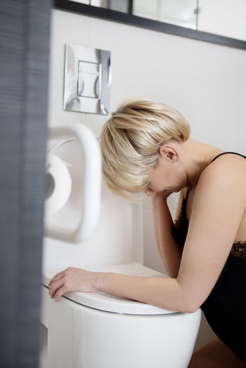 Woman Crying While Leaning On Toilet Seat At Bathroom