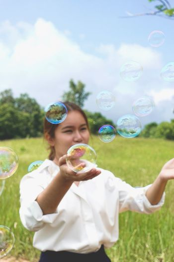 Colorful Field Bubble Wand Bubble Blowing Plant One Person Holding Fragility Nature Day Young Adult Outdoors Portrait Fun Lifestyles Grass