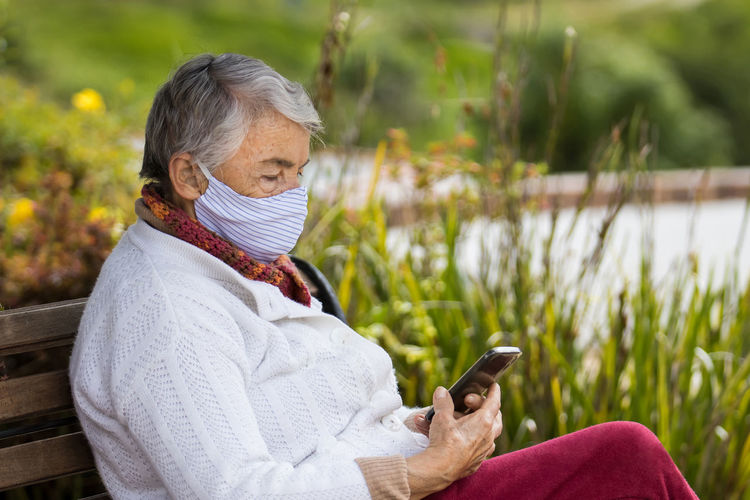 Man holding mobile phone while sitting outdoors