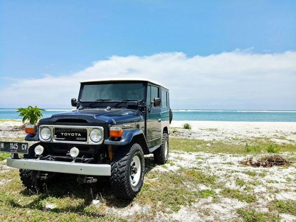Blue Toyota Land Cruiser under the blue sky, accompanied by blue ocean.. Sky 4wd Toyotalandcruiser Bj40 INDONESIA Lombok Island First Eyeem Photo