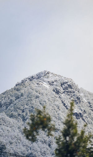 Low angle view of snowcapped mountain against clear sky