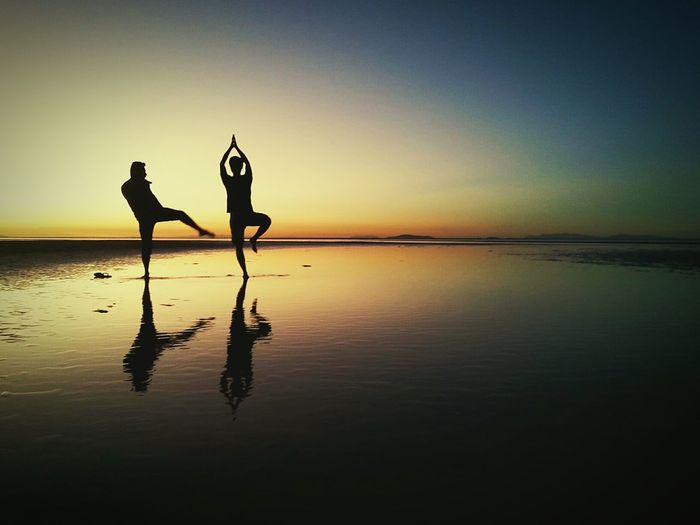 Silhouette man kicking friend performing yoga on beach during sunset