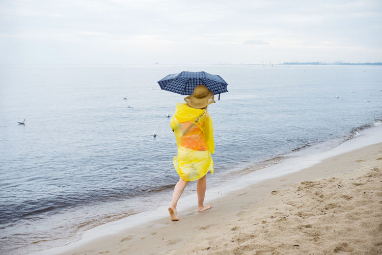 Woman With Umbrella Walking At Sea Shore