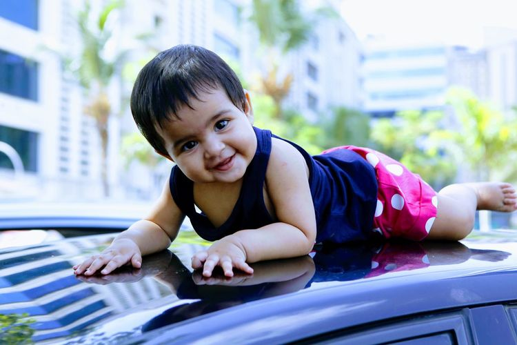Portrait of cute baby girl on car roof
