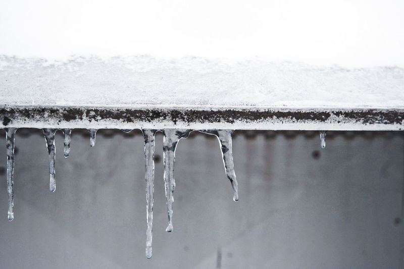 Close-up of icicles on roof during winter