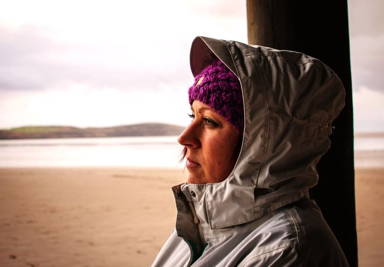 A woman, deep in thought, looking over the coast Seaside Female Cold Sadness Sad Loss Thoughtful One Person Beach Headshot Sand Focus On Foreground Day Knit Hat Outdoors Real People Portrait Sea Lifestyles Close-up One Woman Only Warm Clothing Only Women Sky