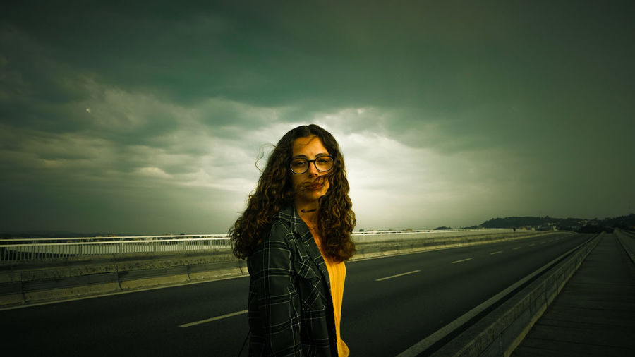 Portrait of young woman standing on road against cloudy sky