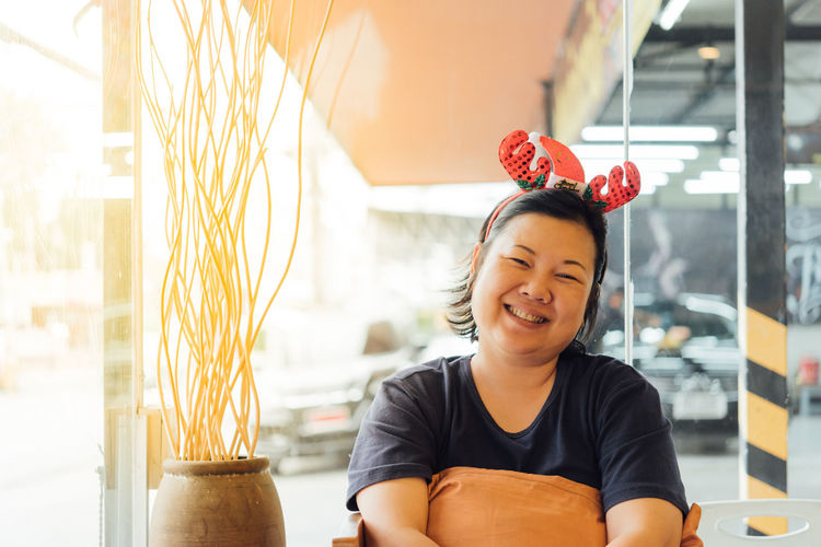 Portrait of smiling woman wearing headband while sitting at cafe