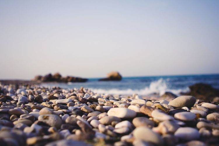Surface level of pebble beach against clear sky