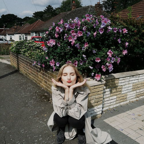 Woman Puckering Lips While Crouching Against Flowering Plants In City