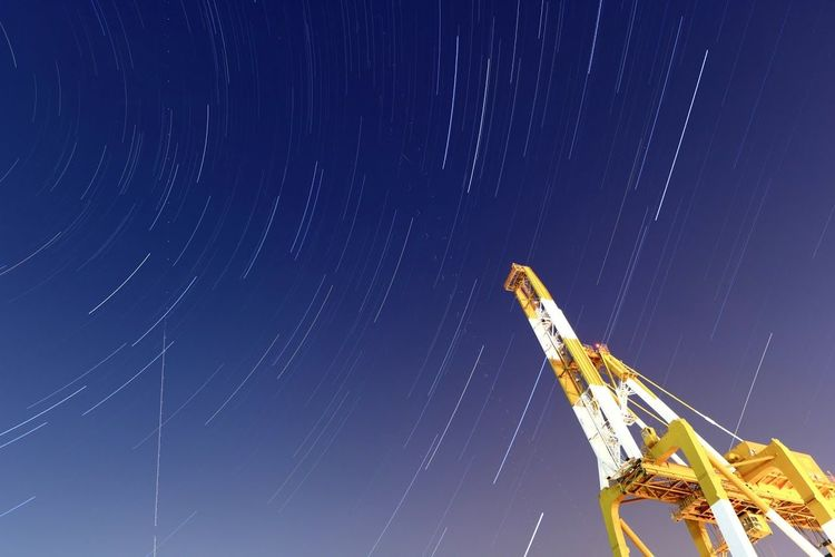 Low Angle View Of Crane Against Star Trail At Dusk