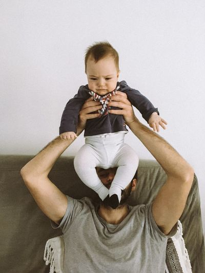 Midsection of father holding baby sitting against white background