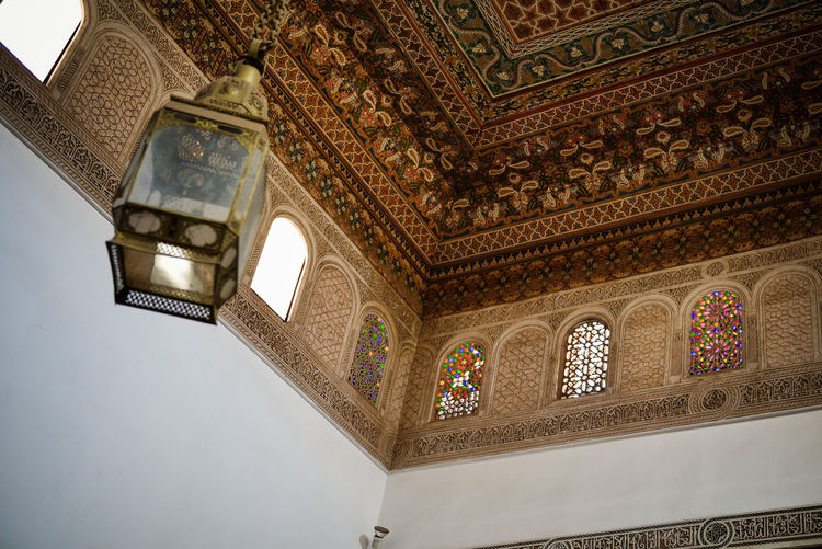 """The Bahia Palace, set in extensive gardens, was built in the late 19th century by the Grand Vizier of Marrakesh, Si Ahmed ben Musa (Bou-Ahmed). Bou Ahmed resided here with his four wives, 24 concubines and many children.[110] With a name meaning """"brilliance"""", it was intended to be the greatest palace of its time, designed to capture the essence of Islamic and Moroccan architectural styles. Bou-Ahmed paid special attention to the privacy of the palace in its construction and employed architectural features such as multiple doors which prevented passers-by from seeing into the interior. Marrakesh, also known by the French spelling Marrakech, is a major city of the Kingdom of Morocco. It is the fourth largest city in the country, after Casablanca, Fez and Tangier. It is the capital city of the mid-southwestern region of Marrakesh-Safi. Located to the north of the foothills of the snow-capped Atlas Mountains, Marrakesh is situated 580 km (360 mi) southwest of Tangier, 327 km (203 mi) southwest of the Moroccan capital of Rabat, 239 km (149 mi) south of Casablanca, and 246 km (153 mi) northeast of Agadir. The ramparts of Marrakesh, which stretch for some 19 kilometres (12 mi) around the medina of the city, were built by the Almoravids in the 12th century as protective fortifications. The walls are made of a distinct orange-red clay and chalk, giving the city its nickname as the """"red city""""; they stand up to 19 feet (5.8 m) high and have 20 gates and 200 towers along them.[90] Bab Agnaou was built in the 12th century during the Almohad dynasty. The Berber name Agnaou, like Gnaoua, refers to people of Sub-Saharan African origin (cf. Akal-n-iguinawen – land of the black). The gate was called Bab al Kohl (the word kohl also meaning """"black"""") or Bab al Qsar (palace gate) in some historical sources. The corner-pieces are embellished with floral decorations. This ornamentation is framed by three panels marked with an inscription from the Quran in Maghrebi script using foliated Kuf"""