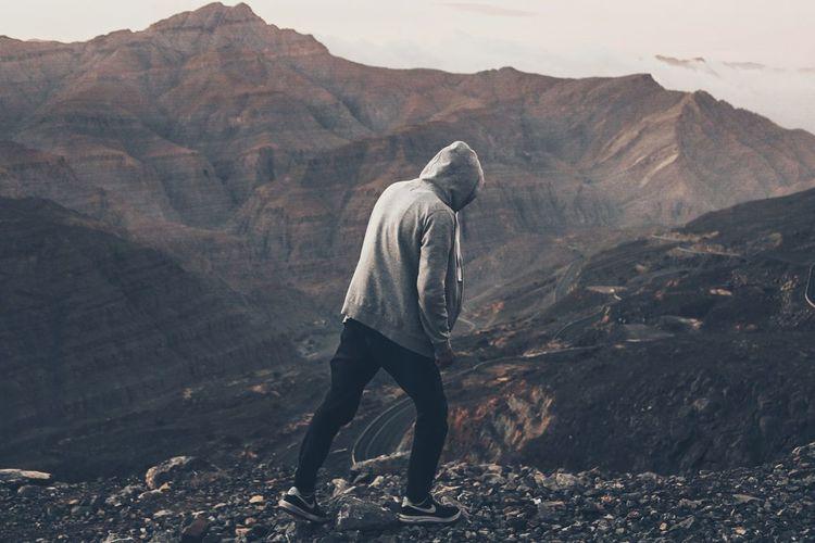 Full length of man standing on desert against mountains