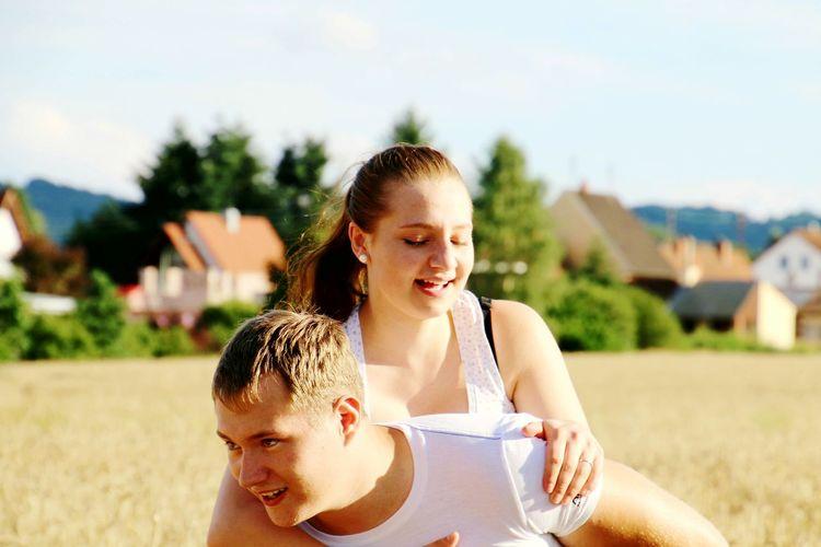Cheerful Couple Enjoying On Field Against Sky