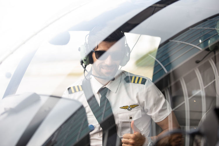 Portrait of pilot gesturing while sitting at cockpit