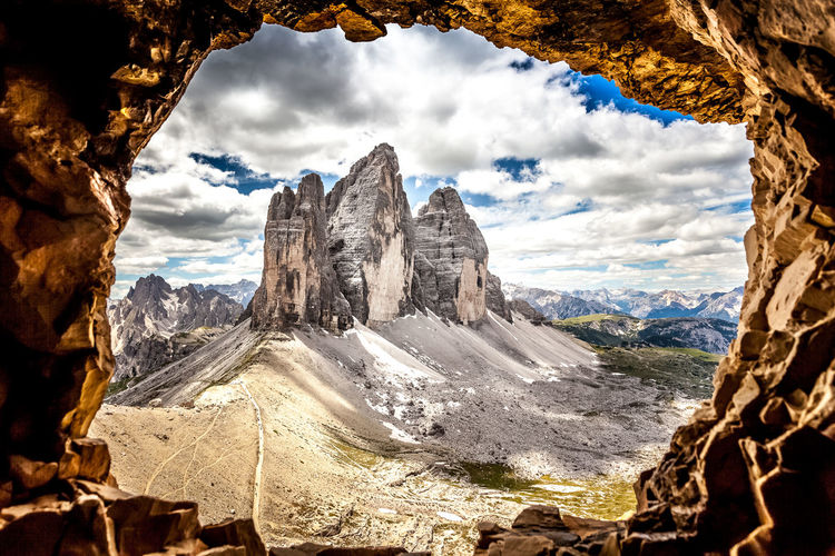 Scenic view of rock formations and mountains seen through hole against sky