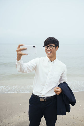 Man photographing while standing on beach