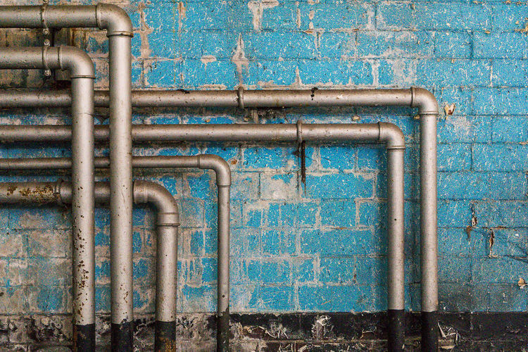 Pipelines on old blue brick wall