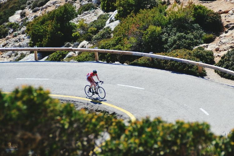 Male triathlete cyclist cycling on road