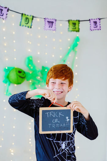 Portrait of smiling boy standing against text