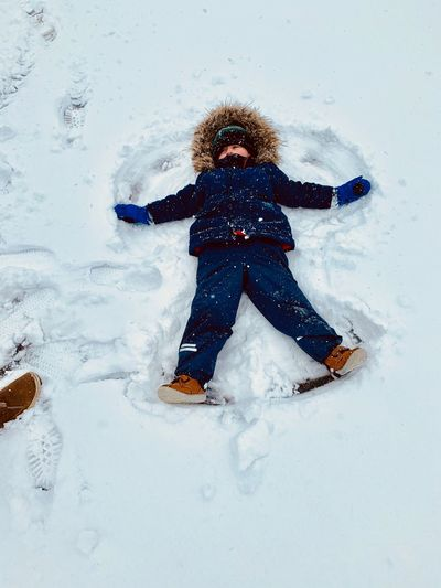 High angle view of boy lying on snowy field