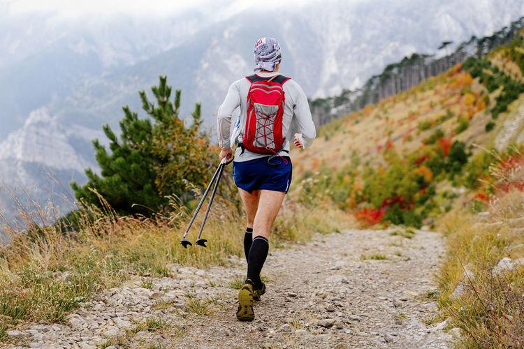 Male athlete run mountain marathon with trekking poles