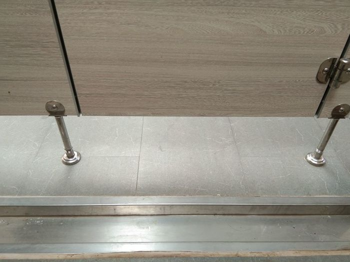 High angle view of metal grate on floor against wall