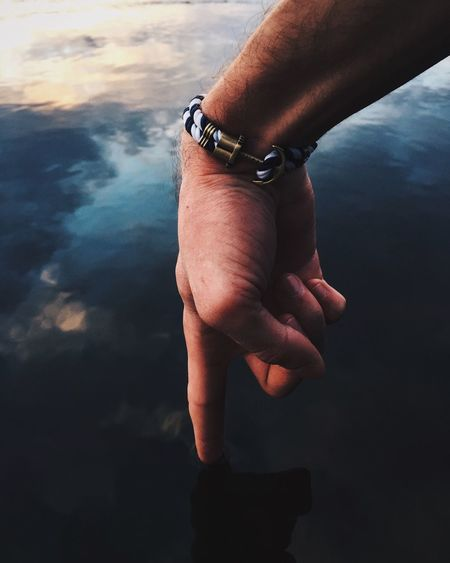 Cropped hand of man touching lake during sunset