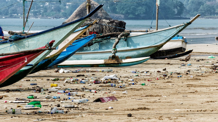 Fishing boats moored by garbage at beach