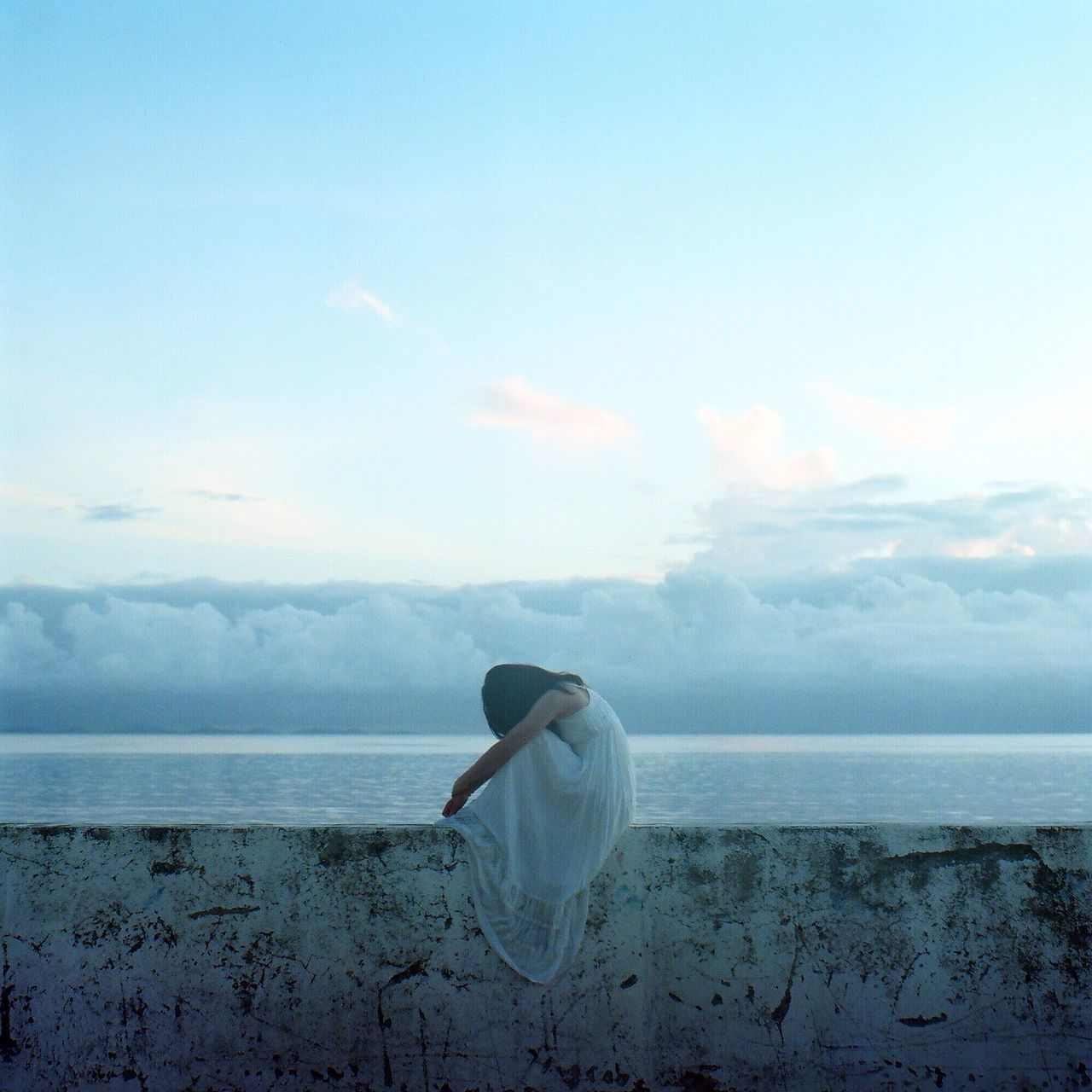Woman Sitting On Surrounding Wall Against Cloudy Sky