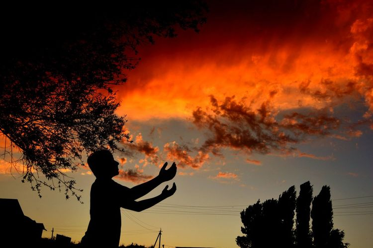 Silhouette Man Gesturing Against Dramatic Cloudy Sky During Sunset