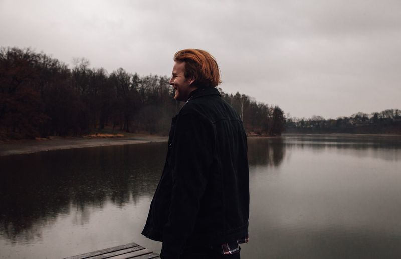 Woman looking away while standing by lake against sky