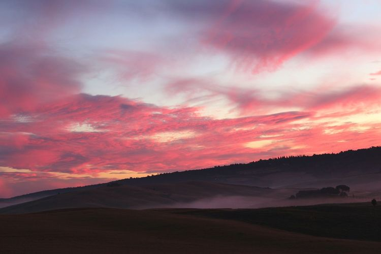Dramatic sky over landscape in tuscany
