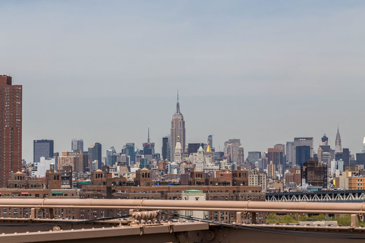 Distant View Of Empire State Building Seen From Brooklyn Bridge