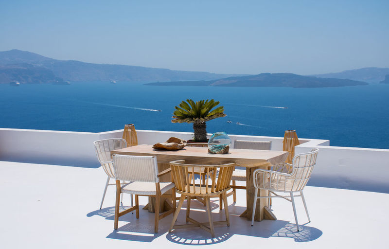 Empty chairs and tables by swimming pool against sky